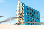 Young Woman Running by Skyscraper