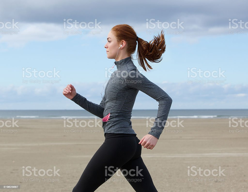 Young woman running by the beach stock photo