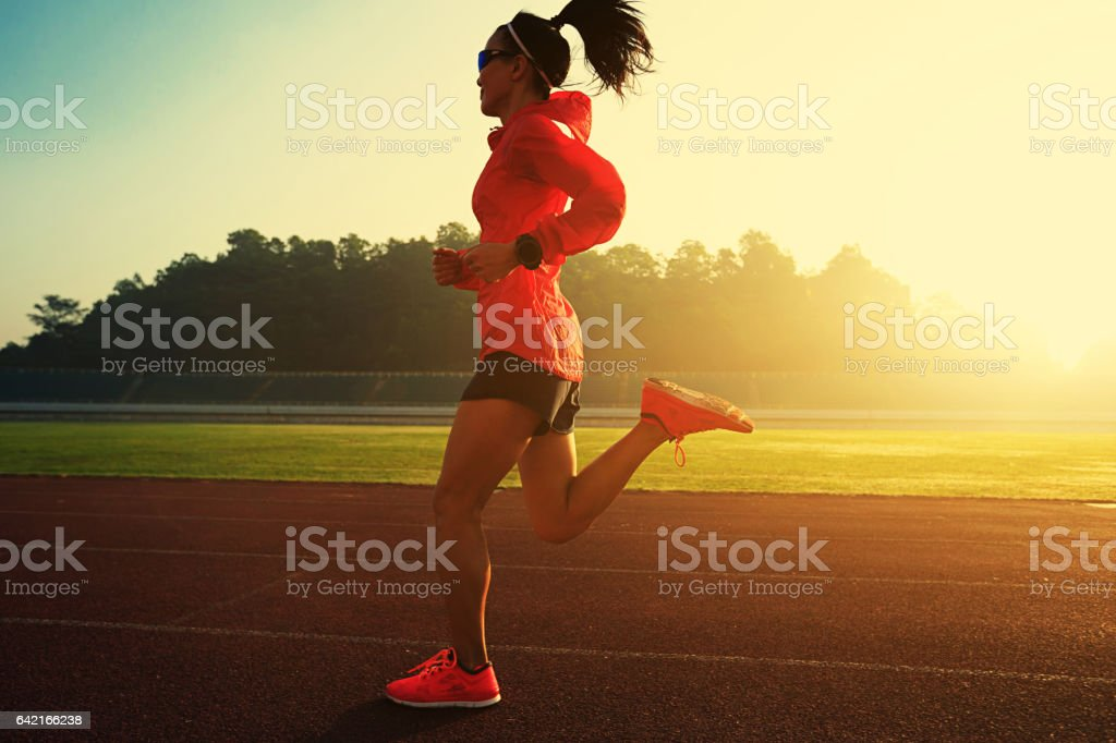 Young woman running during sunny morning on stadium track stock photo