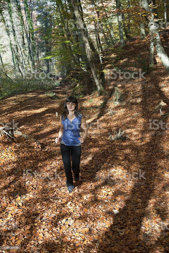 Young Woman Running in Autumnal Forest royalty-free stock photo
