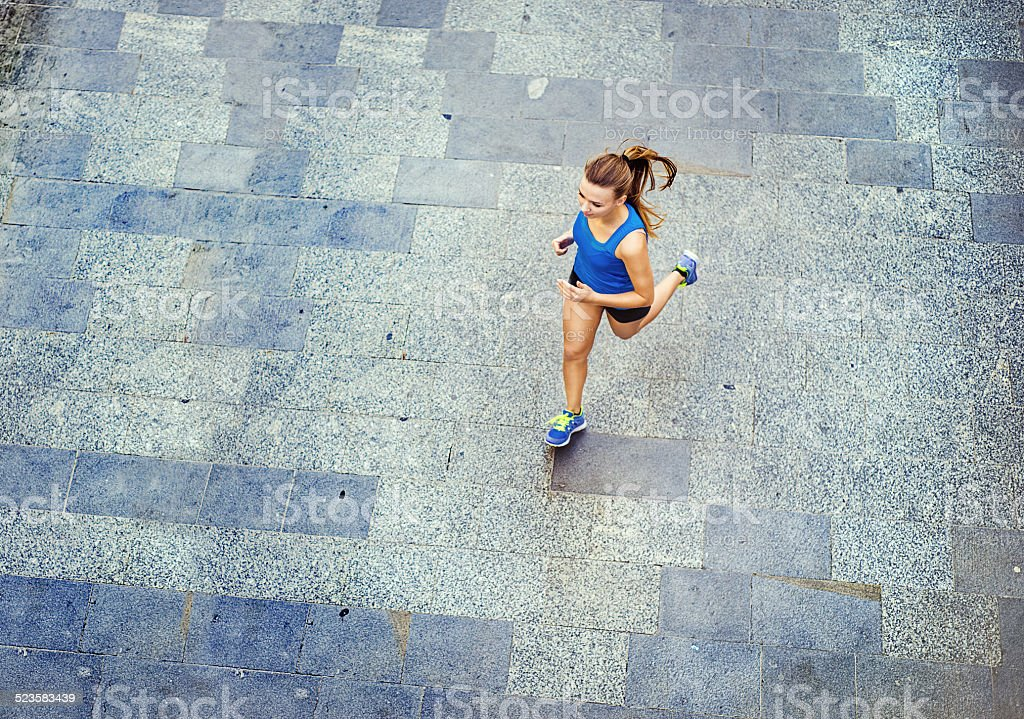 Young woman running in city center stock photo