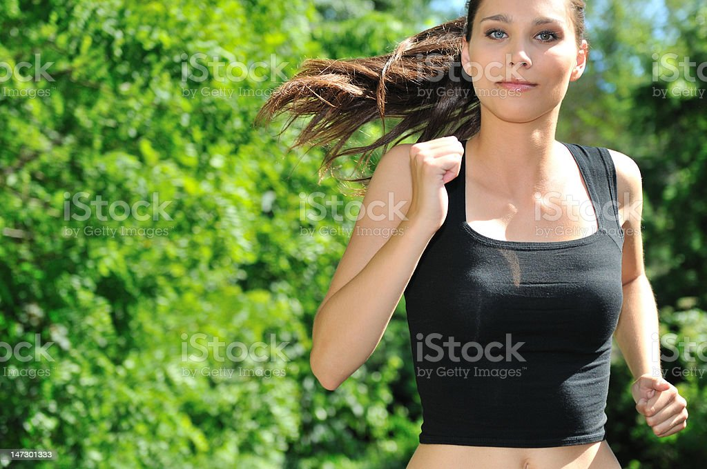 Young woman running in green park royalty-free stock photo
