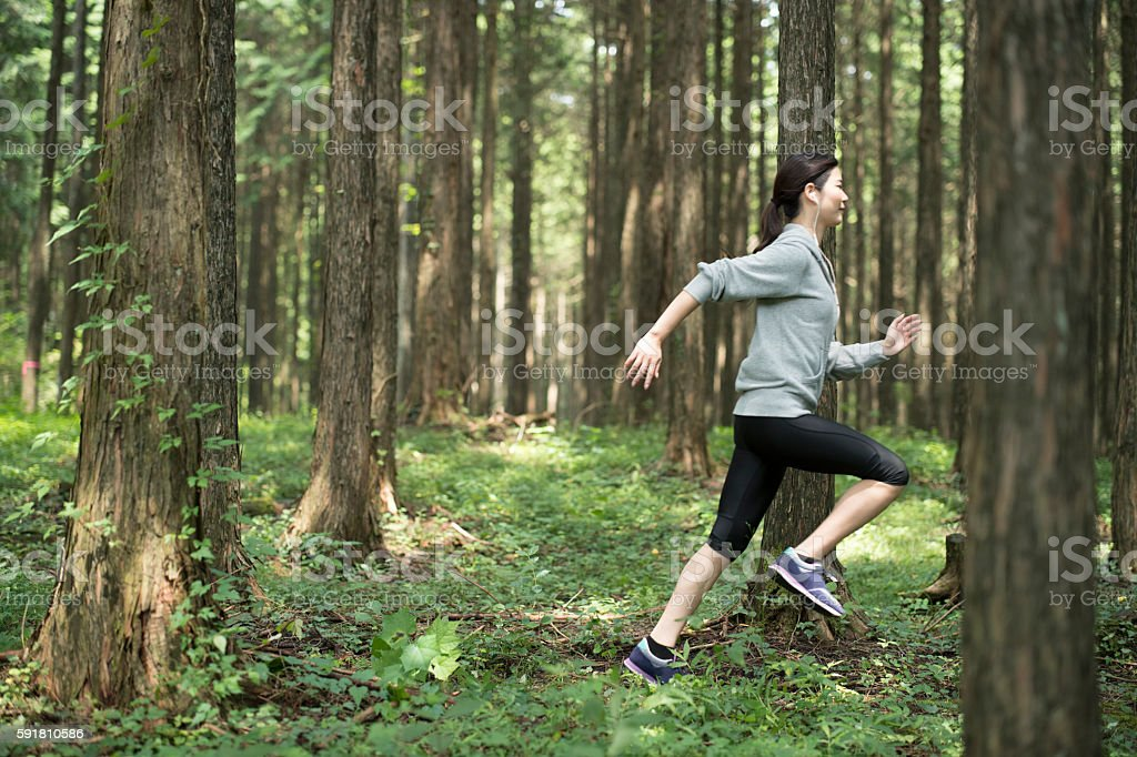 Young woman running in the woods. stock photo