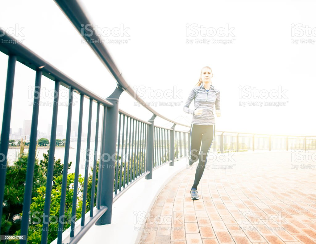 Young woman running in urban setting stock photo