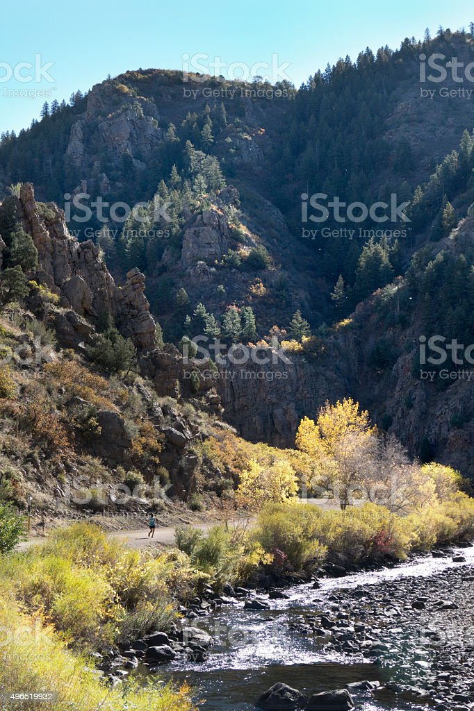 Young woman running in Waterton Canyon Colorado Rocky mountains stock photo