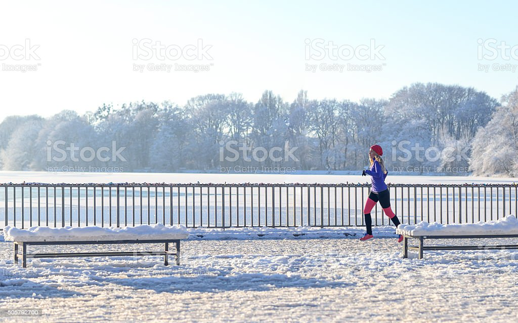 Young woman running in winter snow stock photo