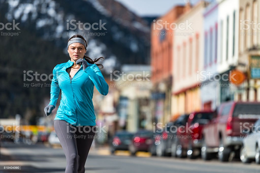 Young Woman Running Jogging in Mountain Town stock photo