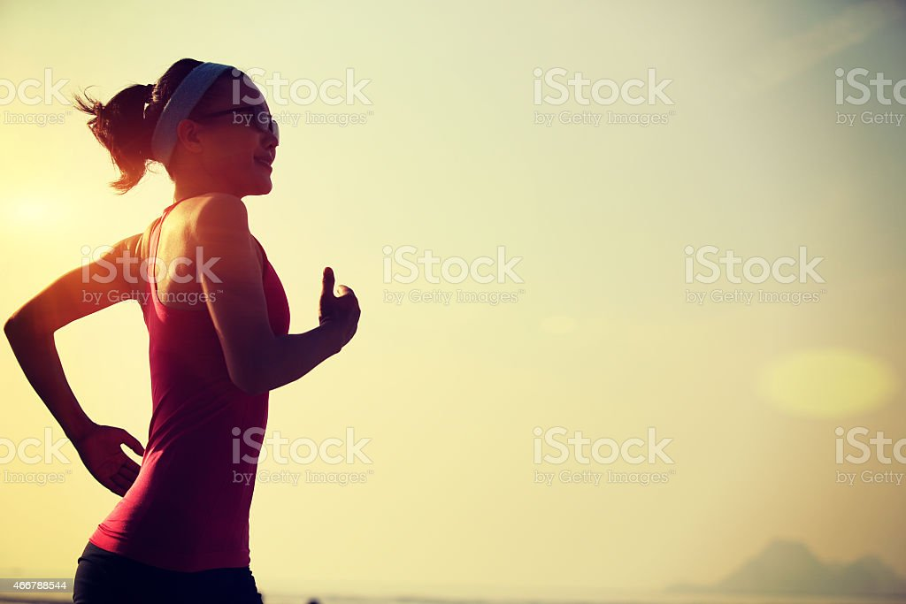 A young woman running on a beach stock photo
