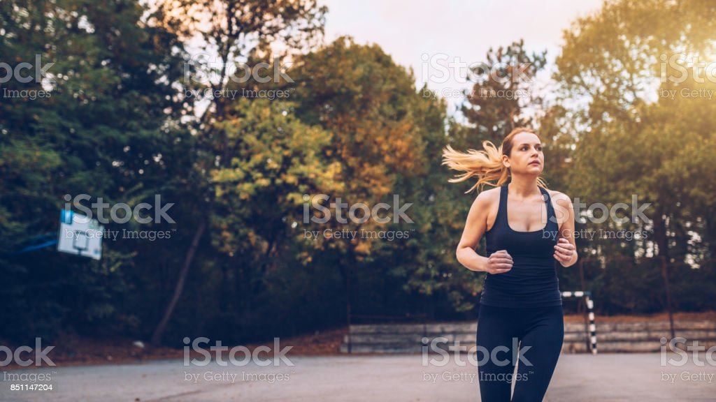 Young woman running on a beautiful autumn day stock photo