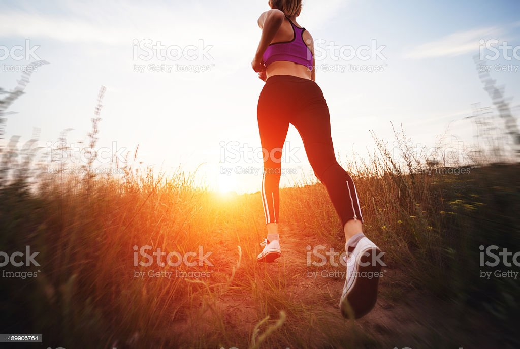 Young woman running on a rural road at sunset stock photo