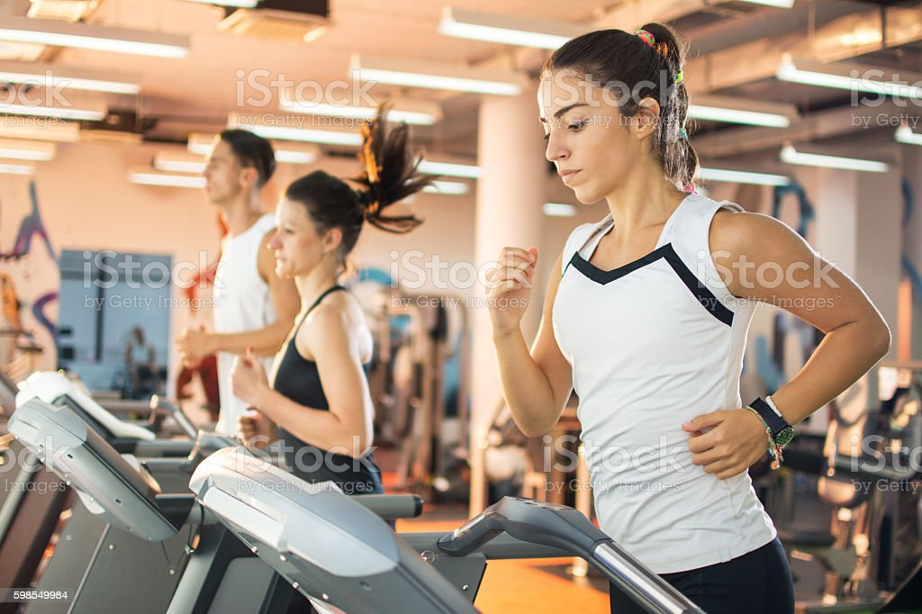 Young woman running on a treadmill at the gym. stock photo
