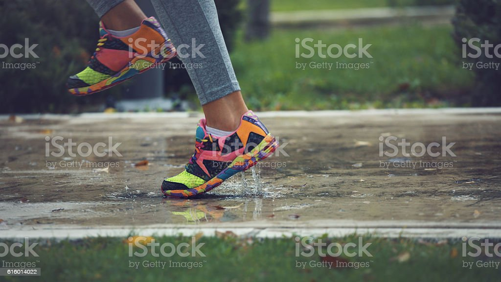 Young woman running on asphalt sports field in rainy weather stock photo