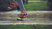 Young woman running on asphalt sports field in rainy weather