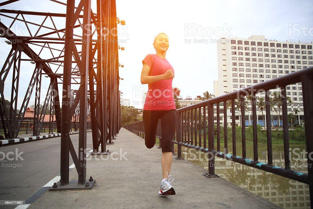 young woman running on iron bridge stock photo