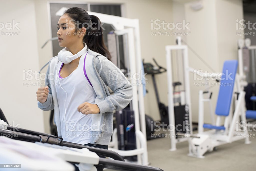 Young woman running on machines. stock photo
