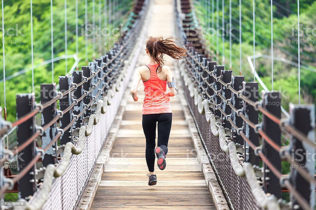 Young woman running on rope bridge stock photo