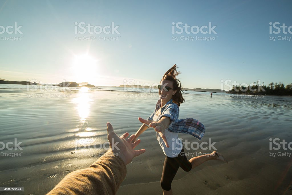 Young woman running on the beach towards a man's hand stock photo