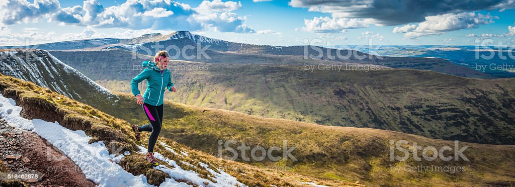 Young woman running on wilderness trails on mountain ridge panorama stock photo