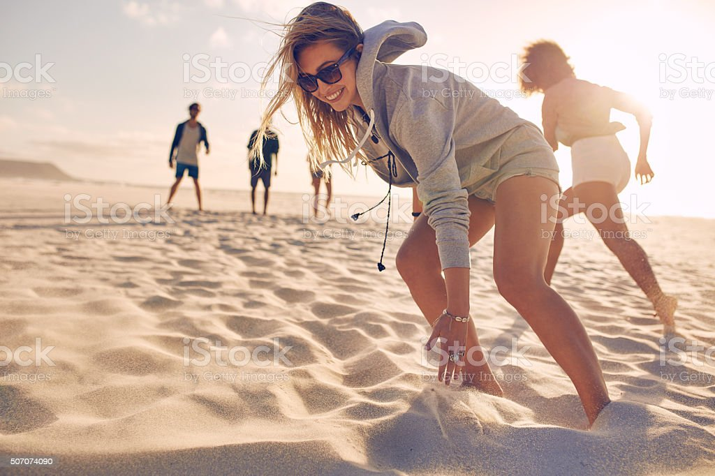 Young woman running race with friends at the beach stock photo