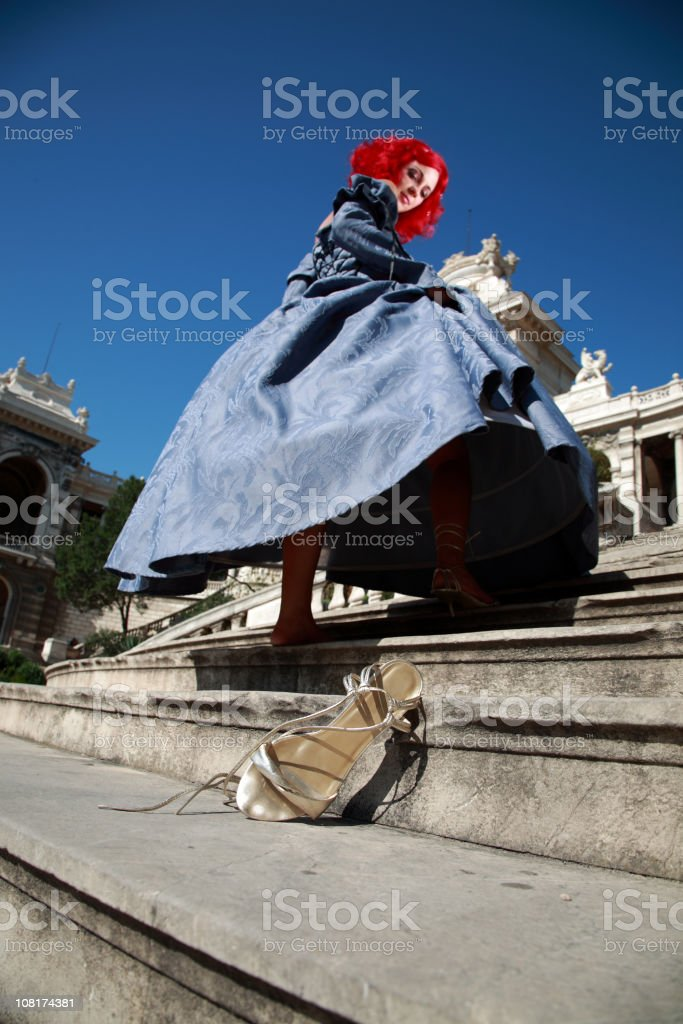 Young Woman Running Up Staircase Loses Shoe stock photo
