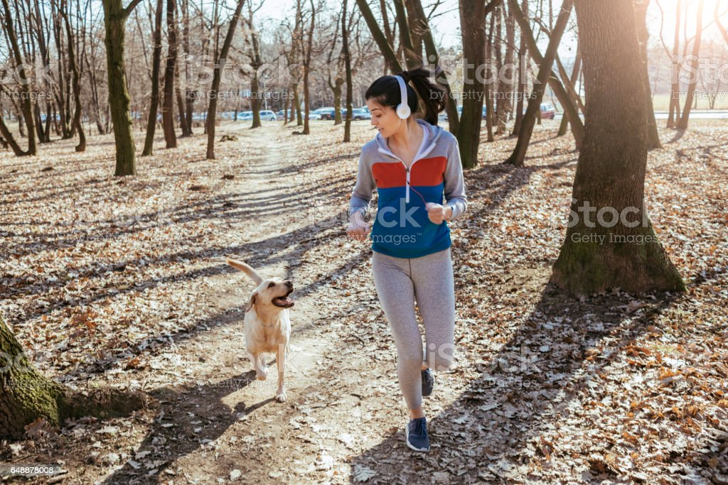 young woman running with her dog stock photo