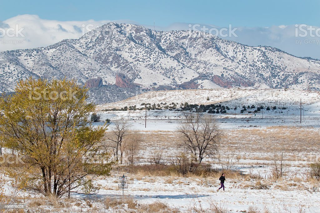 Young woman runs in snowy Fehringer Ranch Park Colorado mountains stock photo
