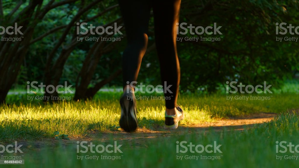 Young woman runs on a footpath - feet level stock photo