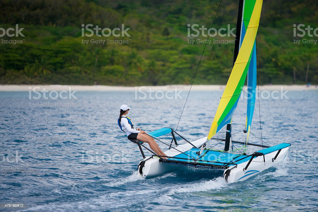 young woman sailing on a catamaran by the Caribbean beach stock photo