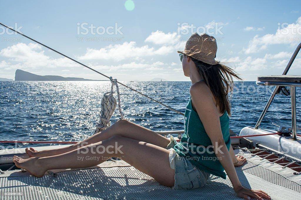 Young woman sailing on catamaran in the sun stock photo
