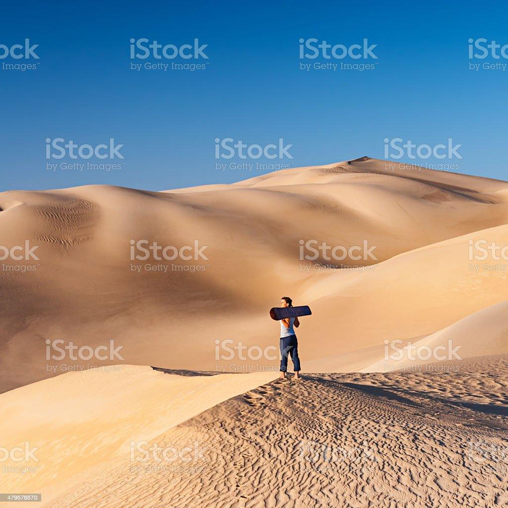 Young woman sandboarding in The Sahara Desert, Africa stock photo