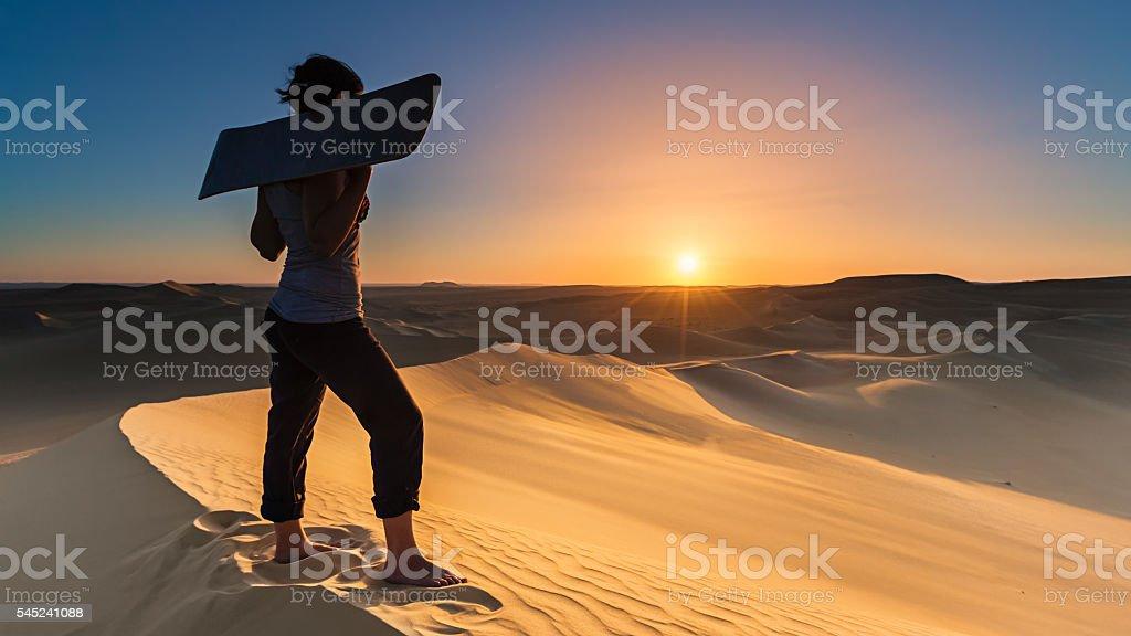 Young woman sandboarding in The Sahara Desert during sunset, Africa stock photo
