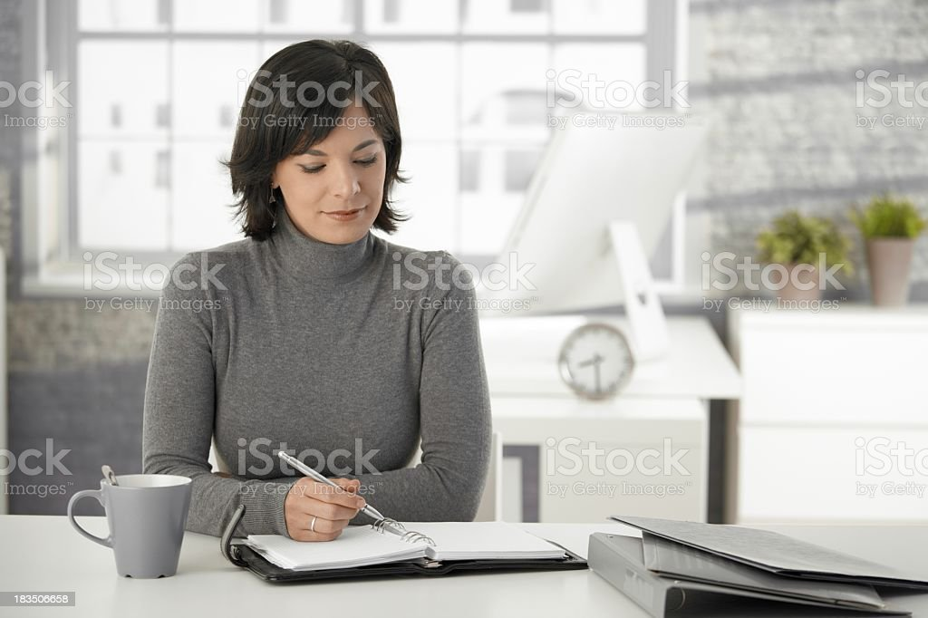 Young woman sat at a white desk holding a pen on a notebook stock photo
