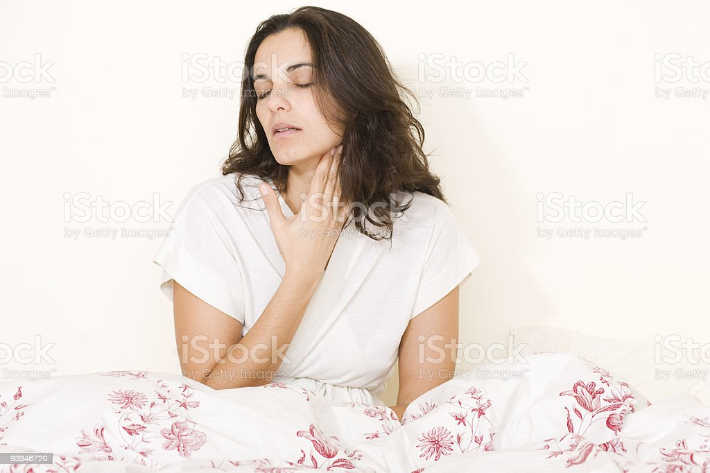 A young woman sat in bed holding her throat stock photo