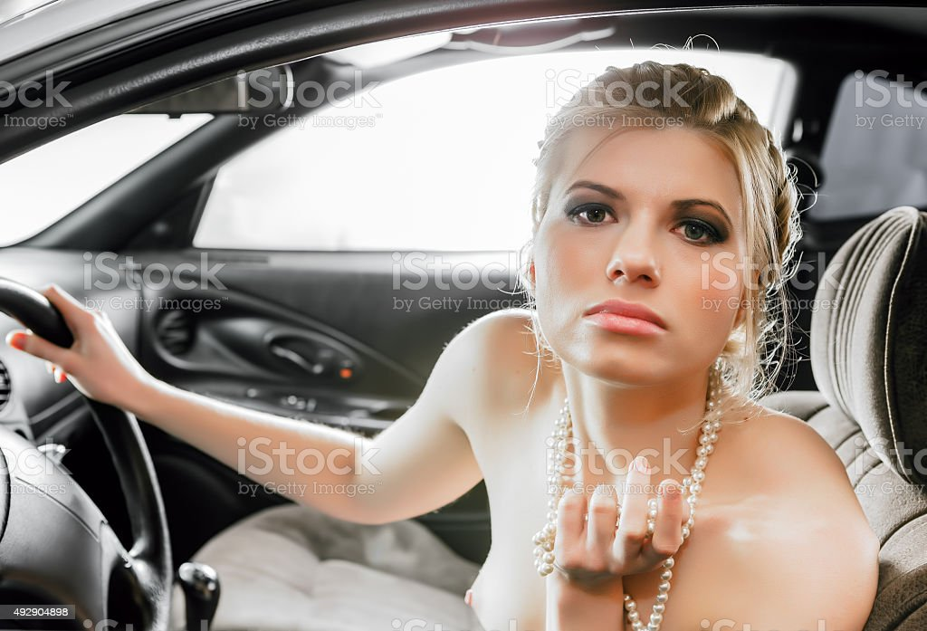 Young Woman Sat In The Drivers Seat of Her Car. stock photo