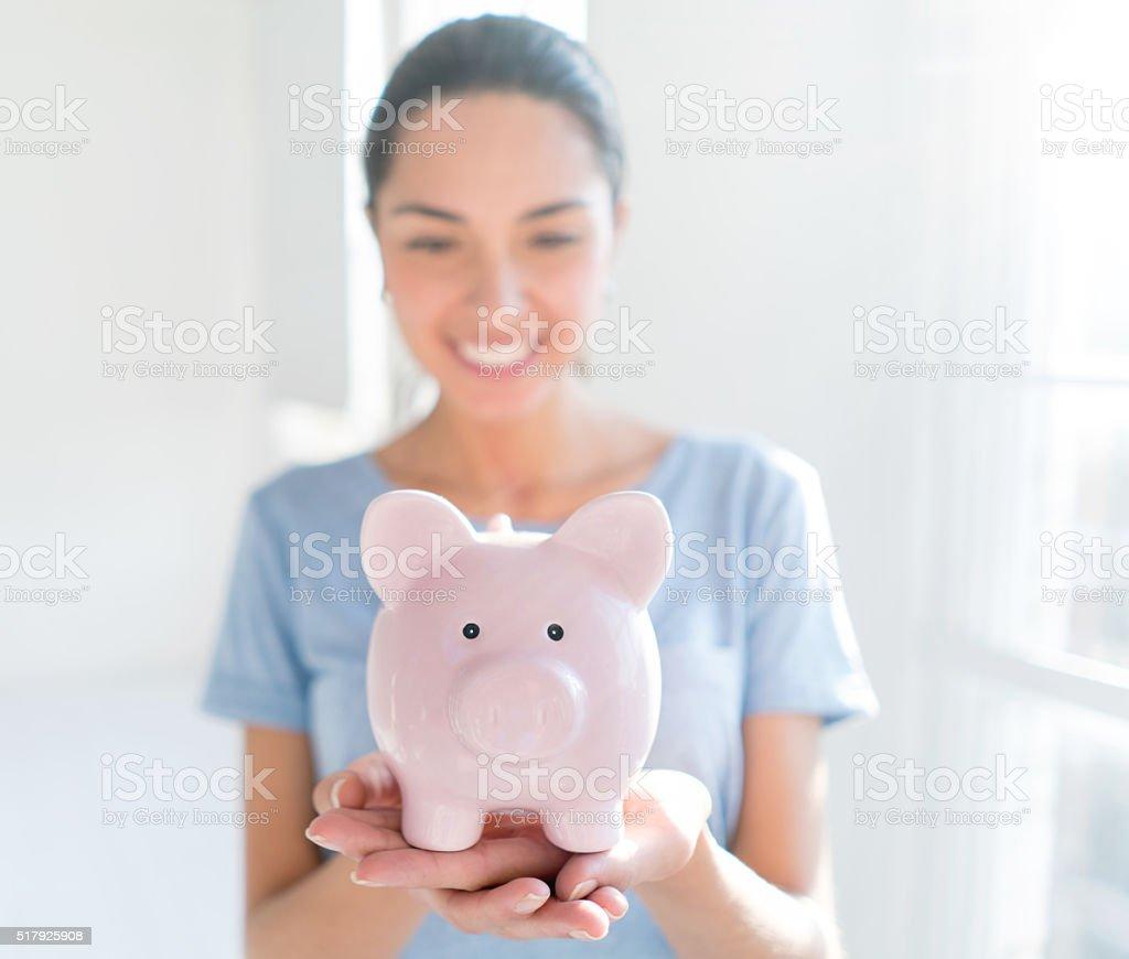 Young woman saving money in a piggybank stock photo