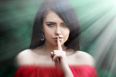 Young woman  saying shh with forefinger on lips. silence gesture