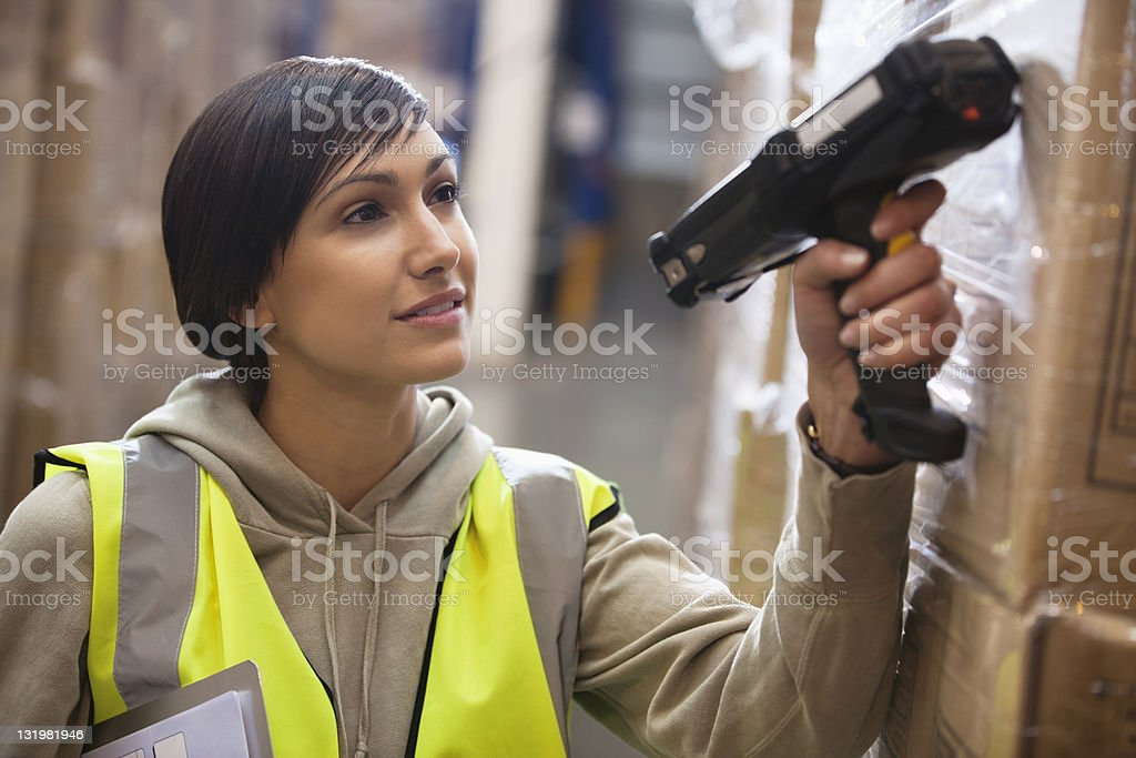 Young woman scanning boxes with bar code reader stock photo