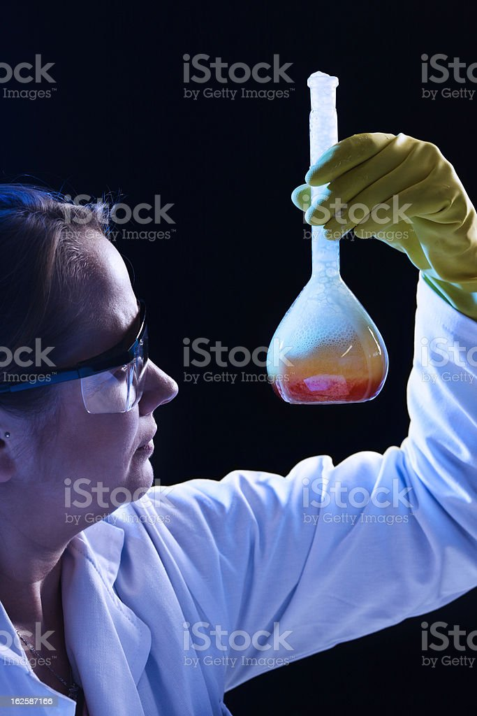 Young woman scientist checks chemical reaction in lab flask royalty-free stock photo