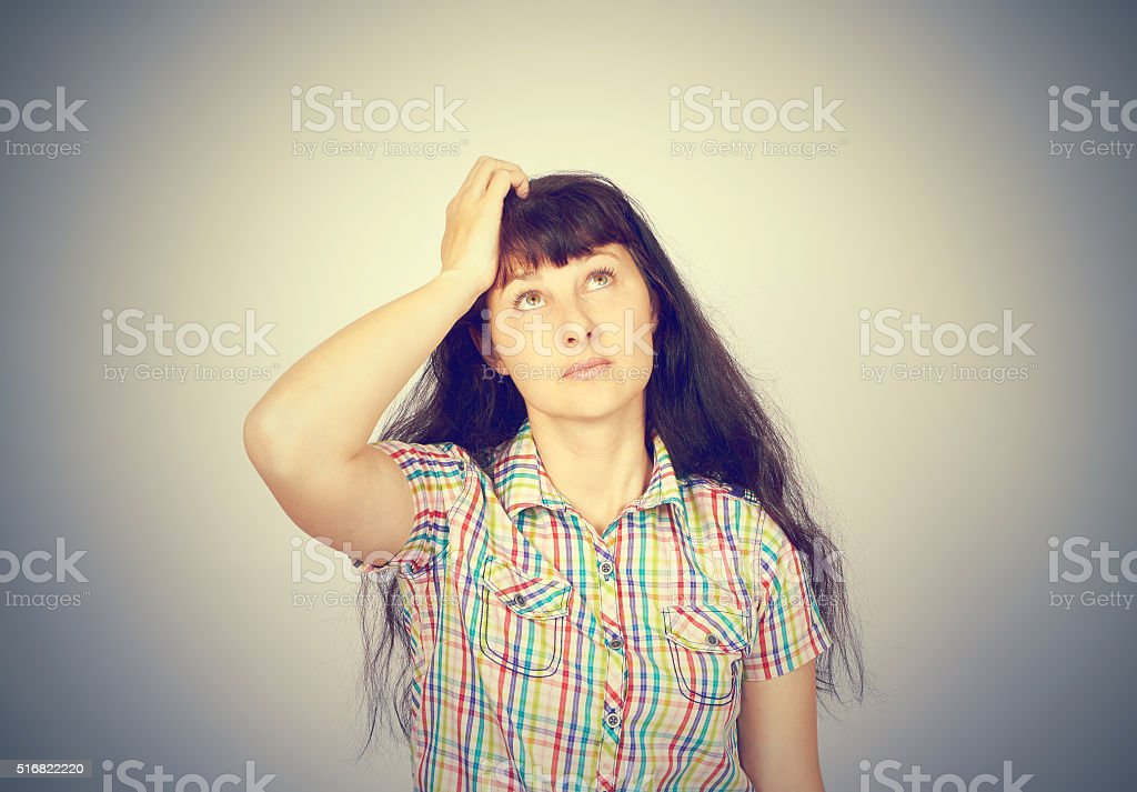 young woman scratching head, thinking daydreaming deeply about stock photo