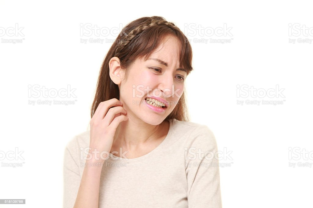 young woman scratching her neck stock photo