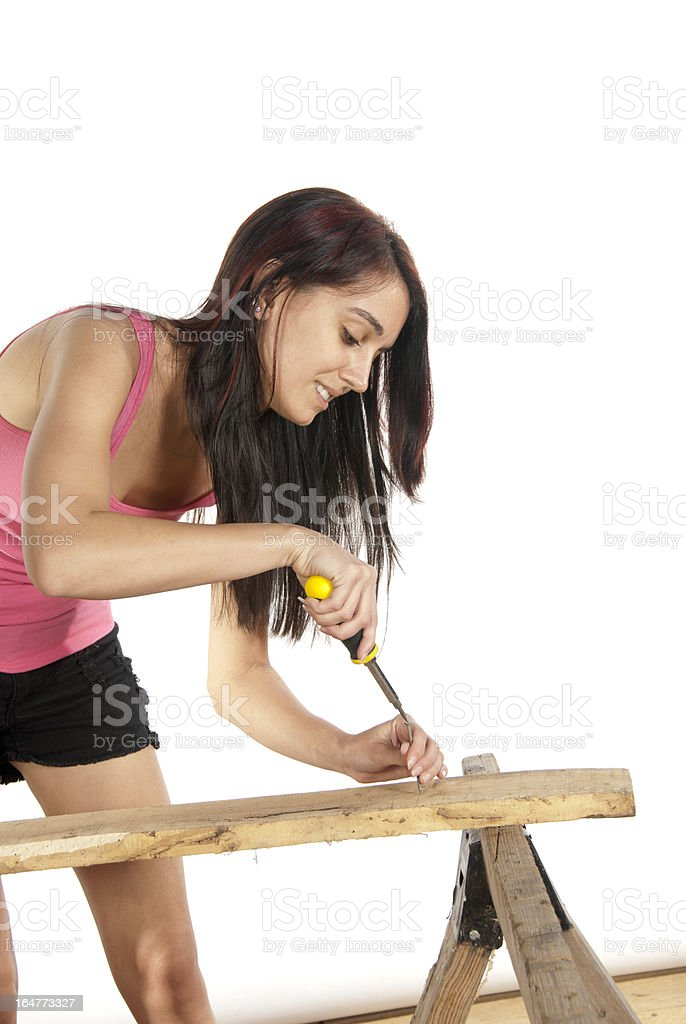Young woman screwdriver putting screw into wood stock photo