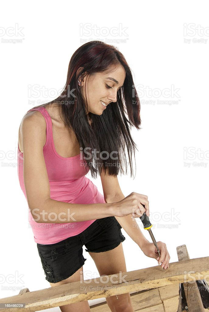 Young woman screwdriver putting screw into wood royalty-free stock photo