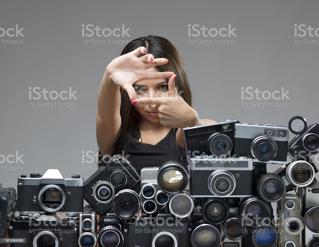 Young woman searching frame composition behind large group of objects stock photo