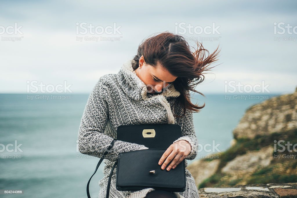Young woman searching in her purse stock photo