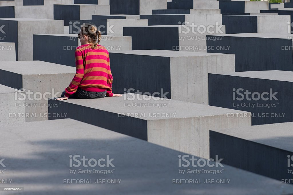 young woman seated in the Holocaust Memorial of Berlin stock photo