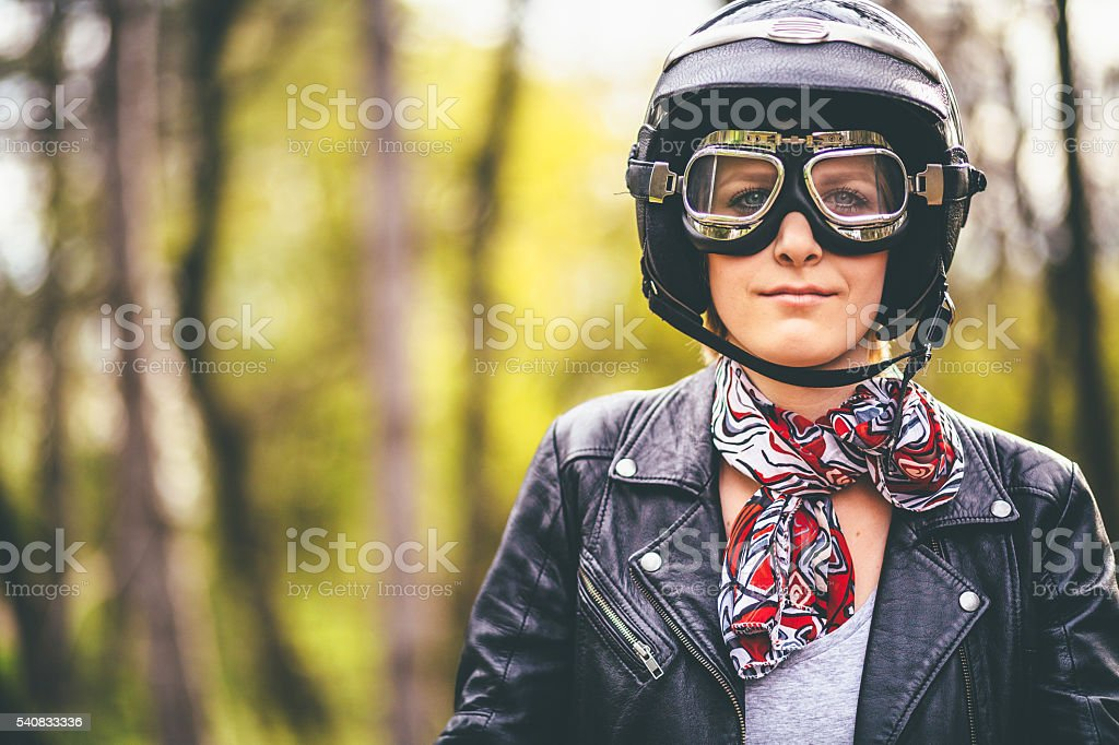 Young woman seating on a motorcycle wearing motorcycling clothes stock photo