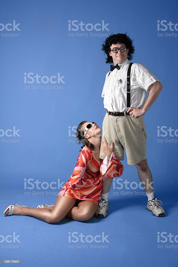 Young Woman Seductively Holding Leg of Nerdy Man stock photo