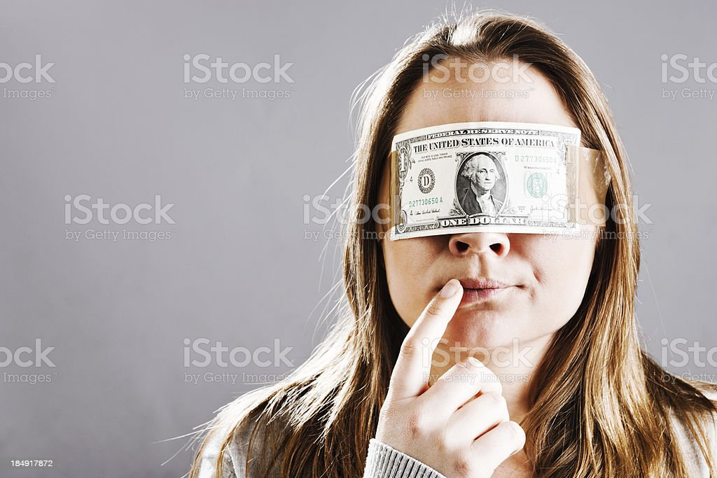 Young woman seems confused by dollar bill blindfold stock photo