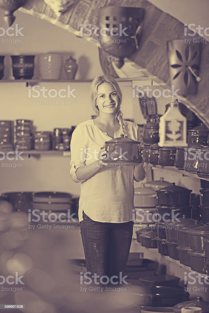 young woman selecting ceramic dish ware in atelier stock photo