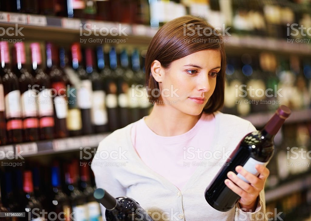 Young woman selecting wine bottles at supermarket royalty-free stock photo